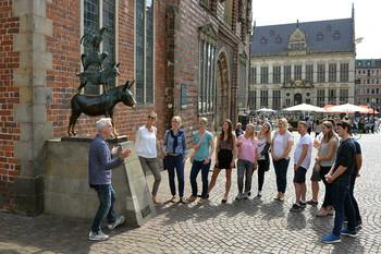 Eine junge Gruppe lässt sich auf einer Stadtführung etwas zu den Bremer Stadtmusikanten erzählen