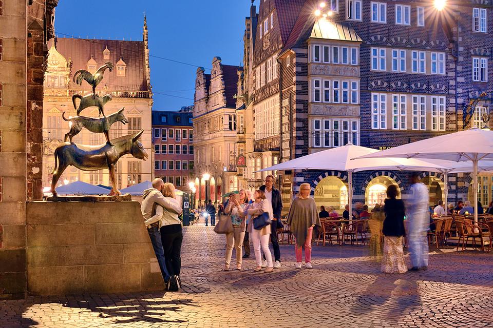 Gäste der Stadt posieren an einem Sommerabend an den Bremer Stadtmusikanten