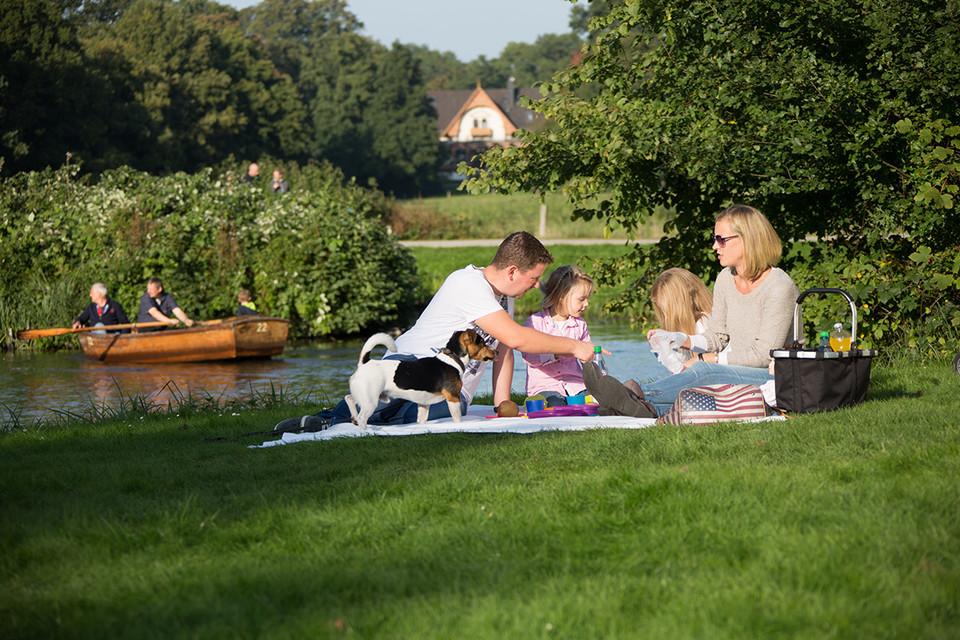 Familie mit Hund beim Picknick im Bürgerpark, dahinter sind Ruderer zu sehen