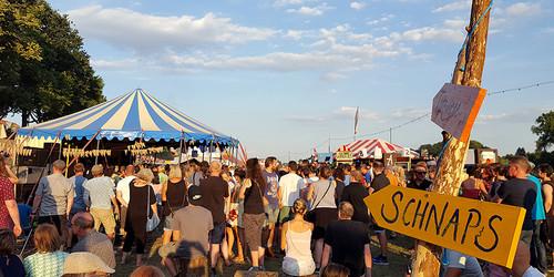 Blick auf das blau-weiße Wohnzimmer-Zelt mit Schnaps-Wegweiser auf der Breminale-Festival an der Weser