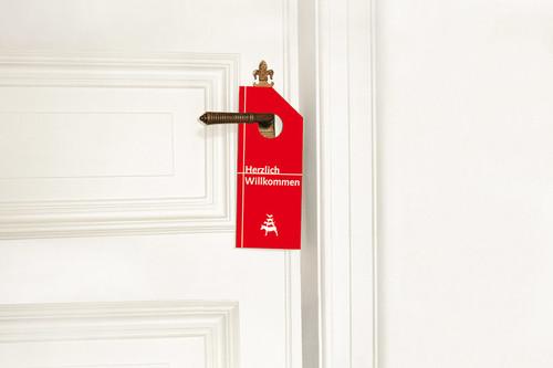 """Schild an einer Hoteltür mit der Aufschrift """"Herzlich willkommen"""""""