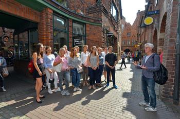 Der Stadtführer erzählt einer Gruppe etwas in der Bremer Böttcherstraße