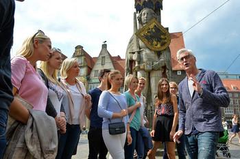 Gruppe junger Menschen lässt sich vor dem Roland etwas über Bremen erzählen