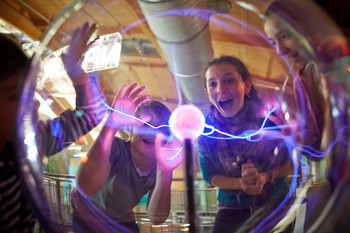 Jugendliche experimentieren an der Plasmakugel im Universum Bremen