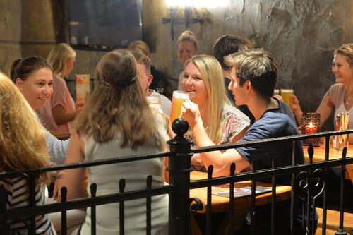 Junge Menschen prosten sich mit Bier in der Gasshausbrauerei Schüttinger zu