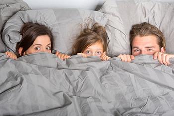 Familie mit Kind zieht sich eine Bettdecke über den Kopf